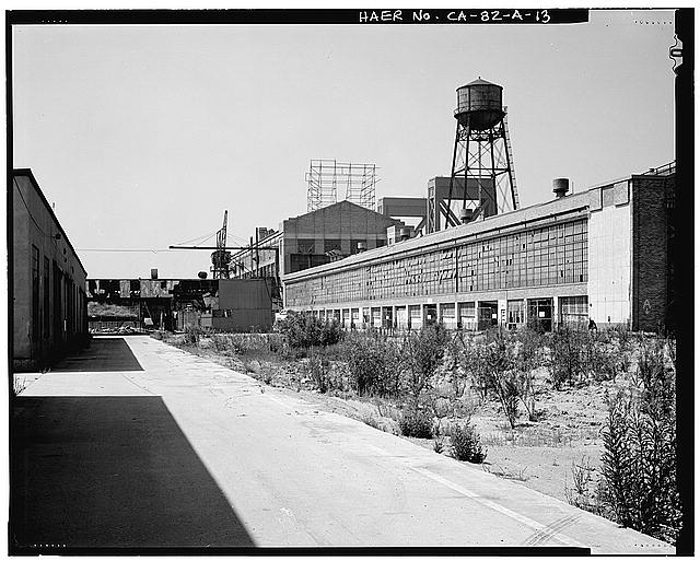 Ford Long Beach Assembly Plant OVERALL SOUTH ELEVATION FROM STORAGE SHED D, SHOWING SHOP A, CRANE, SIGN STRUCTURE, AND WATER TOWER. NOTE TOWERS OF BRIDGE BEHIND PLANT.
