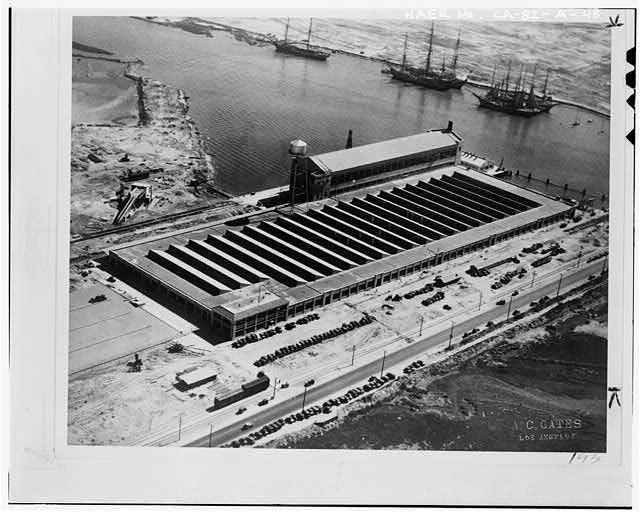 AERIAL VIEW OF THE FORD MOTOR COMPANY ASSEMBLY PLANT, PRIOR TO CONSTRUCTION OF THE PRESSED STEEL BUILDING, NOTE THE CLIPPER SHIPS IN THE BACKGROUND, AND THE OIL WELLS IN THE UPPER LEFT CORNER