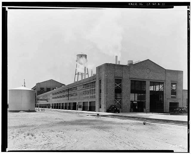 Ford Long Beach Assembly Plant Apr 24, 1931, EXTERIOR-PRESSED STEEL BUILDING, NORTH AND EAST SIDES, WAREHOUSE IN BACKGROUND, RAILROAD SPUR IN FOREGROUND, BONDERITE TANK AT LEFT
