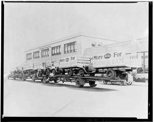 Ford Long Beach Assembly Plant Sep 24, 1931, EXTERIOR-OFFICE BUILDING AND ASSEMBLY BUILDING, WEST SIDE, SHOWING TRUCKS AND TRAILORS LOADED WITH NEW TRUCKS DISPLAYING SIGNS MORE FORDS FOR HOOVER DAM