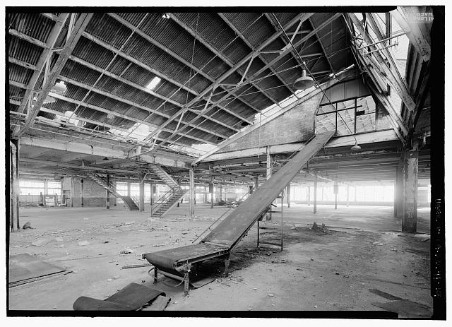 Ford Richmond Assembly Plant VIEW TO SOUTHWEST OF FIRST FLOOR SHOWING CONVEYOR FOR MOVING MATERIAL TO SECOND FLOOR. (NOTE: THIS IS NOT AN ORIGINAL CONVEYOR FOR MOVING BODY PARTS) STAIRS IN BACKGROUND LEAD TO SECOND FLOOR VIA TOILET ROOM NO. 4 AND COAT ROOM AT MEZZANINES LEVEL SITUATED BETWEEN THE TWO SETS OF STAIRS. THERE ARE THREE OTHER TOILET/COAT ROOM MEZZANINES TO THE NORTH LOCATED ALONG THE WALL BETWEEN THE FIRST AND SECOND FLOORS, BEHIND AND TO THE LEFT OF THE STAIRS IS A FREIGHT ELEVATOR SHAFT.