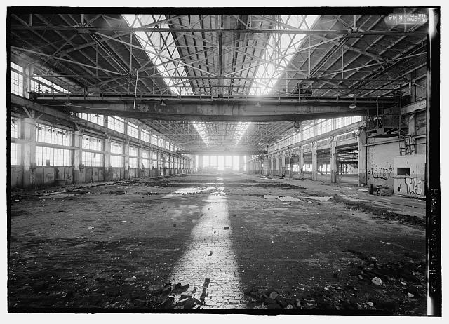 Ford Richmond Assembly Plant VIEW TO WEST OF INTERIOR OF CRANEWAY WITH TOW TRAVELING BRIDGE CRANES (ONE OVERHEAD IN FOREGROUND AND ONE OVERHEAD IN BACKGROUNDS). NOTE WOOD BLOCK PAVING ON THE FLOOR. FIRST FLOOR ASSEMBLY AREA IS THE SPACE IN THE BACKGROUND ON THE RIGHT.